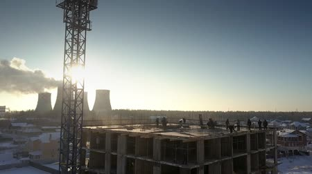 cement floor : aerial view huge crane stands against morning sun hidden by white steam near people silhouettes on building upper floor Stock Footage
