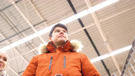 appear : low angle shot closeup handsome guy pushes shopping cart walks along shelves girl face appears behind back Stock Footage