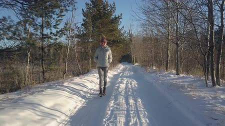 winter day : aerial view beautiful young woman in warm jacket enjoys hike in old winter forest covered with snow on day Stock Footage