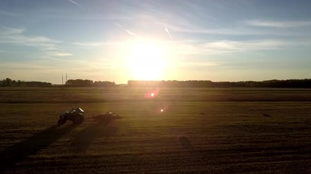 kolektor : flycam rises over tractor and square baler silhouettes shows tremendous panorama of autumn sunset above field