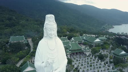 montanhoso : bird eye flight huge buddha statue in religious complex with triangular roofs temple buildings near forestry hills