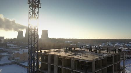 inacabado : aerial view people silhouettes stand on unfinished building level against sunrise from behind operating cooling towers
