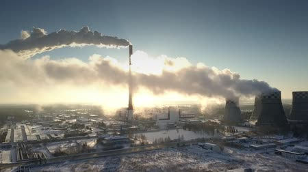 electric ray : aerial view white steam clouds creep close to ground hiding morning sun on electric power station
