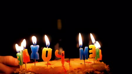 vagabundo : slow motion close backside view on birthday cake letters with lit candles and man hand with lighter