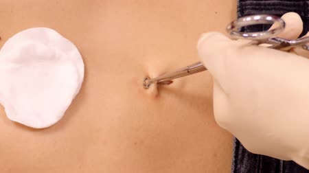 зажим : slow motion close view master holds clamps fixing navel tissue for piercing and cotton disks lie on client belly