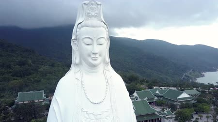 sorriso largo : breathtaking close upper view huge smiling buddha statue against green forest under cloudy sky in Danang