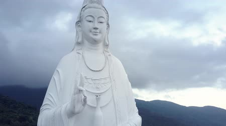 montanhoso : aerial motion from large buddha statue head along body in festive clothing to hands against hills hidden in thick clouds Vídeos