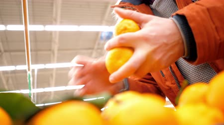 mandarinka : slow motion low angle shot young man in red jacket takes fresh aromatic tangerines in supermarket