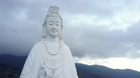 naszyjnik : exciting aerial close view white buddha statue with necklace against hills under grey cloudy sky in Vietnam Wideo