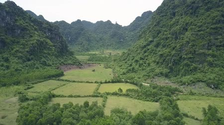 cercar : pictorial aerial view green fields surrounded by rocky hills with green trees under overcast sky on nasty day