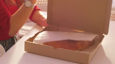 seçkinler : close view young woman opens cardboard box with prepared khachapuri pie on white table lit by sunlight
