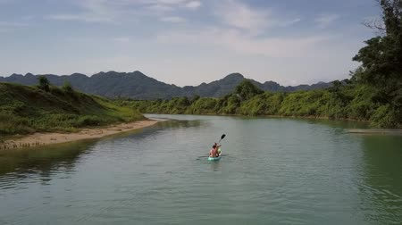 kano : wonderful upper view tourists in canoe sail on calm river near green trees against hills on summer day