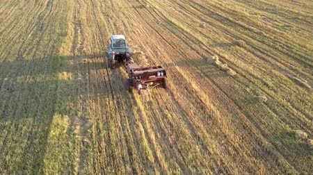 collected : drone follows tractor and square baler pushes up collected straw bale on harvested field at sunset in autumn