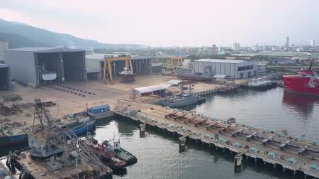 embarcadero : NHA TRANG, KHANH HOAVIETNAM - MAY 06 2018: Close motion above berth industrial zone with boats drifting on rippling water under grey sky in morning aerial on May 06 in Nha trang