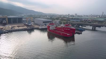 졸졸 흐르는 : NHA TRANG, KHANH HOAVIETNAM - MAY 06 2018: Large red ship moors on rippling water surface at pier against highway bridge and big city under cloudy sky aerial on May 06 in Nha trang 무비클립