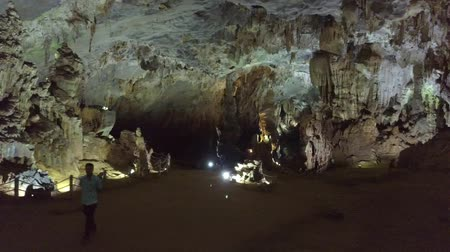 sudeste : man tourist walks along wonderful spacious illuminated cave with huge stone formations view from flycam