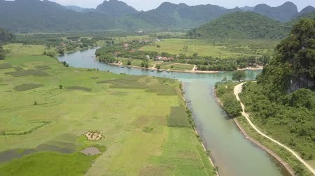 estreito : tranquil narrow river meanders along valley with green fields against pictorial distant mountains aerial view