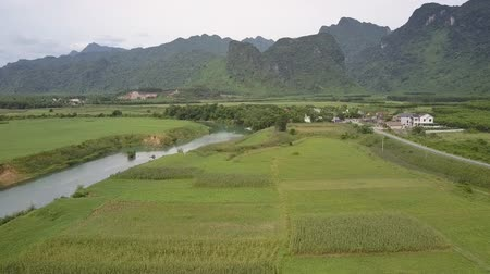 pinda s : exciting aerial view green peanut fields between narrow river and village buildings against forestry hill tops