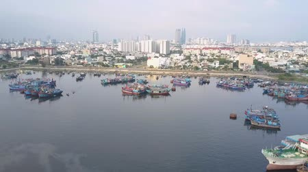 moorage : flying camera zooms out large city and moorage crowded with different boats along highway in morning