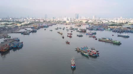 moorage : flying camera zooms out fishing boats drifting at moorage water surface against big city under morning sky Stock Footage