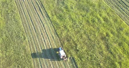 mow : close motion above machine on immense field with traces from cut grass against beautiful landscape in countryside Stock Footage