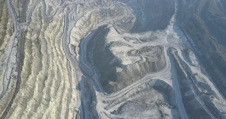 minério : beautiful upper view steep cascade asbestos pit grey hills and machines operating on site in early morning