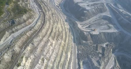 azbest : beautiful upper view steep cascade asbestos pit grey hills and machines operating on site in early morning