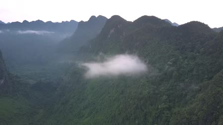 preso : small gray clouds stuck among high steep mountain peaks with green thick tropical forest aerial view