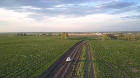 ground : passenger car moves fast along ground road in direction to little village at sunset under boundless dark navy sky Stock Footage