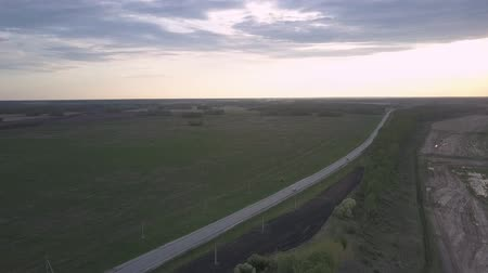 дороги : distant white car speeds along wide highway among green fields and forest belts at twilight bird eye view Стоковые видеозаписи