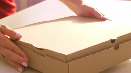 элита : close view young long haired woman hands with manicure take cardboard box from white table in restaurant