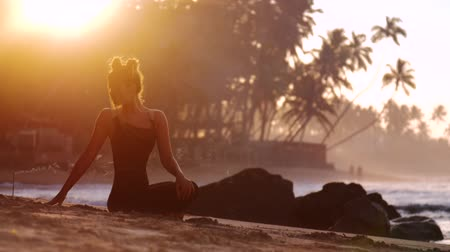 meditál : young woman silhouette meditates doing yoga on sandy ocean beach against sun rising from behind palms extreme slow motion. Concept wellness lifestyle meditation