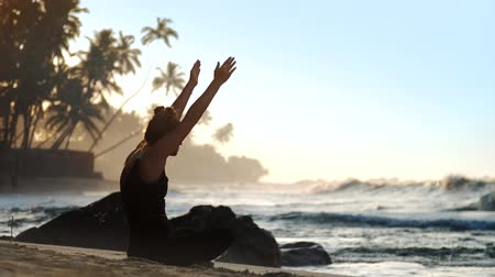 incienso : exciting lady silhouette in tracksuit meditates with hands on knees against blue endless ocean in morning extreme slow motion. Concept meditation wellness lifestyle