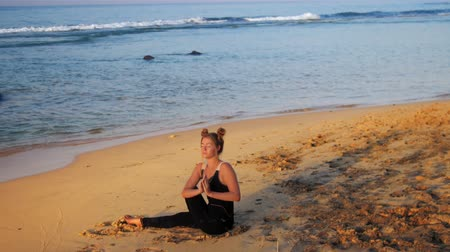 hatha : exciting lady in black sits on sand beach puts hands in Salutation Seal meditating against blue foaming ocean waves slow motion. Concept spiritual practices wellness lifestyle teacher