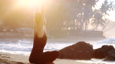hatha : exciting lady raises hands doing yoga on sandy ocean beach with brown stones in morning at bright back sunlight slow motion. Concept fitness sport yoga healthy lifestyle
