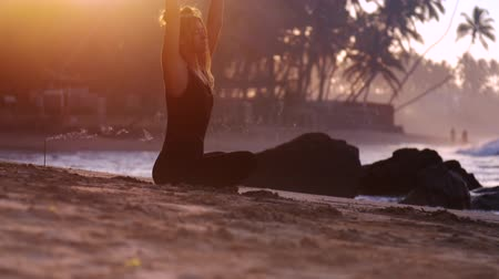 позы : beautiful girl with closed eyes turns in incense stick smoke on sand against ocean waves and stones at sunrise extreme slow motion. Concept yoga meditation and wellness lifestyle Стоковые видеозаписи