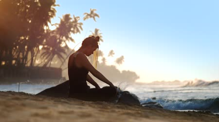 chakra : young woman silhouette meditates in lotus pose on sand beach against blue ocean waves and palms extreme slow motion. Concept spiritual practices wellness lifestyle Stock Footage
