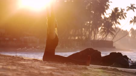 meditál : wonderful barefoot lady meditates in yoga asana on sand beach near incense stick under bright sun rays extreme slow motion. Concept meditation wellness lifestyle