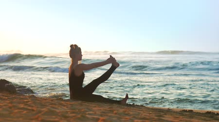 meditál : wonderful lady meditates doing yoga on orange sandy beach lit by sun against blue endless ocean extreme slow motion. Concept fitness sport yoga healthy lifestyle