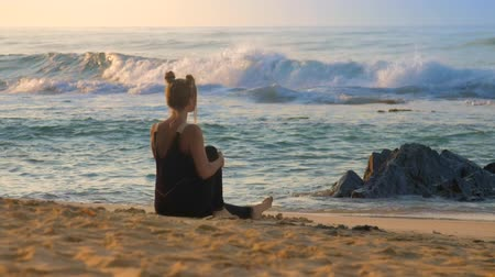 meditál : wonderful lady in black dressing meditates on yellow sand beach against blue foaming ocean waves backside view extreme slow motion. Concept spiritual practices yoga wellness lifestyle
