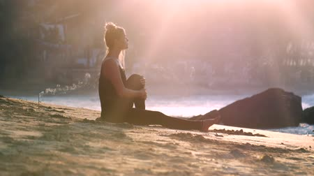 meditál : exciting girl silhouette lit by rising sun rays meditates in yoga position on sand beach at ocean and rocks extreme slow motion. Concept spiritual practices yoga wellness lifestyle teacher guru