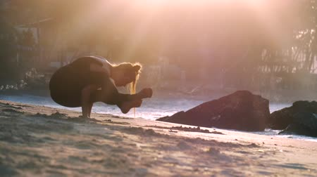pozíció : young beautiful woman stands on hands in yoga pose Firefly under bright morning sun near ocean and brown stones extreme slow motion. Concept fitness sport yoga healthy lifestyle