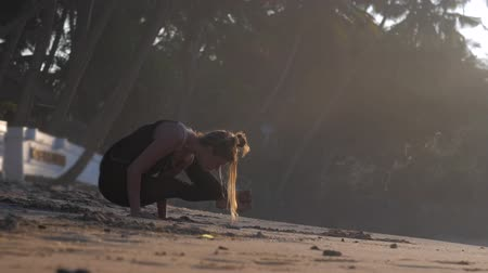 meditál : young woman meditates standing on hands in yoga pose Firefly on sand beach lit by sun against dark shady palms slow motion. Concept meditation fitness sport yoga