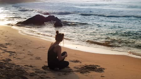 bum : slim lady in black tracksuit sits on sand beach meditating in yoga position backside view slow motion. Concept health lifestyle and meditation
