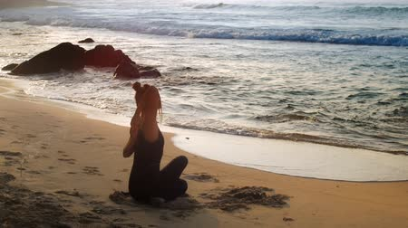 chakra : tremendous lady meditates practicing yoga pose Cow Face on sand beach against ocean waves and brown rocks in morning extreme slow motion. Concept fitness sport yoga meditation Stock Footage