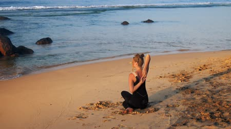 sea cow : beautiful girl practices yoga exercise Cow Face on yellow sand beach against blue ocean backside view st sunrise extreme slow motion. Concept spiritual practices fitness wellness lifestyle