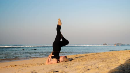 conserva : lady in black tracksuit keeps balance with raised legs on sand beach in yoga pose Rejuvenation near ocean extreme slow motion. Concept fitness sport yoga healthy lifestyle