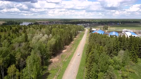 utiliteit : cross-over drives to small village along gray asphalt road among dense forests under blue sky with clouds aerial view. Concept countryside and rural population extinction Stockvideo