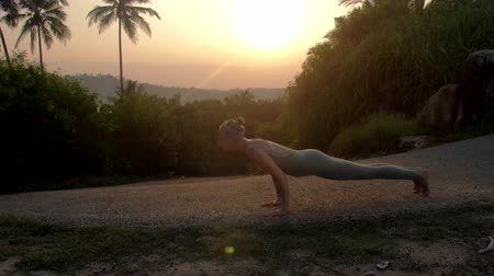 saudação : strong girl silhouette changes positions of sun salutation yoga complex on empty track in early morning side view slow motion. Concept fitness yoga wellness lifestyle