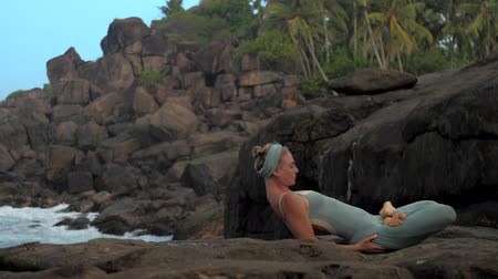kap : yoga teacher in tracksuit gets into padma matsyasana on large flat rock on sea shore in morning extreme slow motion. Concept yoga meditation and spiritual practices